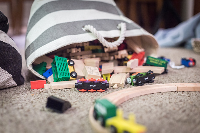 Toddler learning toy (a wooden train set tumbles from bag.)