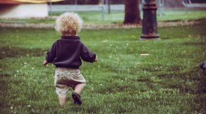 baby walking over some grass