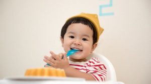asian toddler in a highchair wearing a party hat