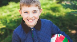 Boy holding a ball and smiling