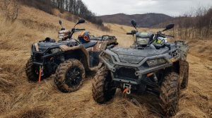 2 ATVs parked side by side on a dirt track