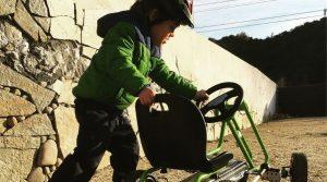 Young boy pushing a go-kart along