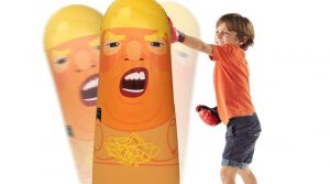 child punching an inflatabe donald trump
