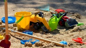 Lots of sand box toys in some sand