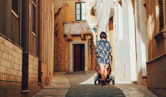 Lady walks child in stroller.