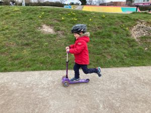 Small boy rides three wheeled scooter