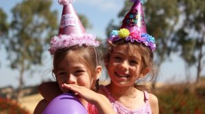 Two girls wearing party hats and holding balloons