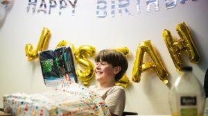 9 year old boy opening birthday presents