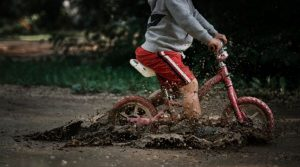 Photo of a young boy riding a balance bike through a muddy puddle