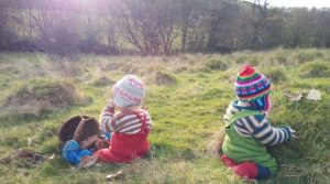 Photo of two boys having a picnic in nature