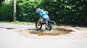 Photo of a boy riding a balance bike through a puddle