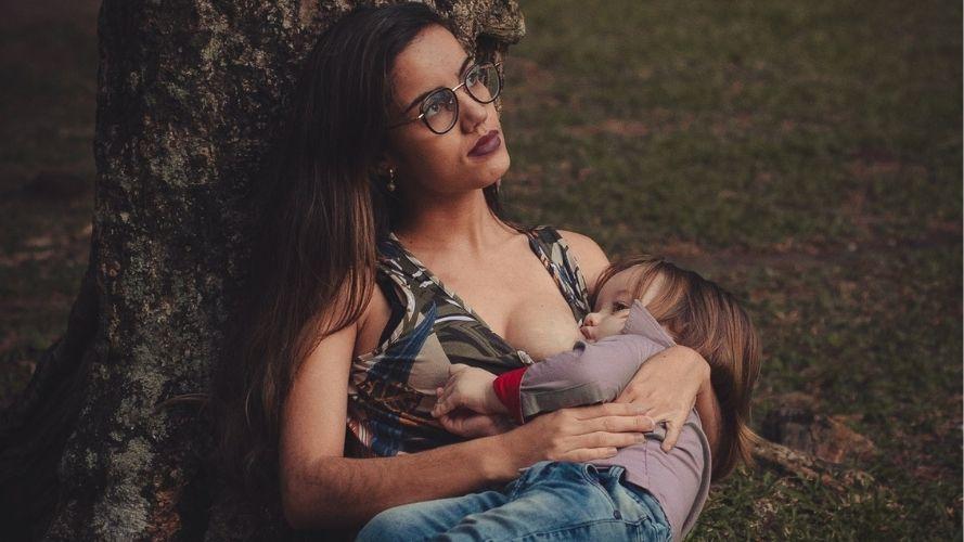 Photo of a stylish mom nursing under a tree